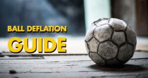 A deflated soccer ball sitting on a wooden floor
